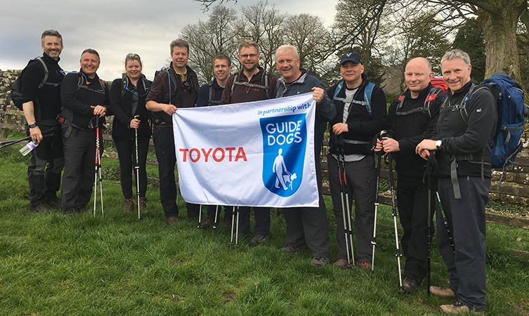 The Toyota GB Directors pose in the countryside holding a Toyota and Guide Dogs flag.