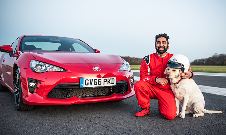 Dr Amit Patel and his guide dog, Kika, sit in front of a red Toyota GT86,